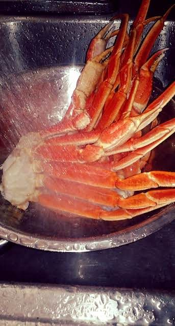 Rinse ice from frozen crab legs, and place in the strainer or drainer inserted...