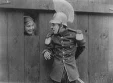 Chaplin has some great sight gags in the movie, like a hilarious table dance & sword fighting near the end. His boyish charm & role of soldier is a winning combination.  One peculiar stunt involves a group of men pushing a huge door back & forth forever until it finally falls over to clearly reveal it as a movie prop & gives a glimpse of his movie set.  #burlesque #film #history #CharlieChaplin #BurlesqueOnCarmen   Check out our #NeoBurlesque #documentary #BurlesqueAReemergence…