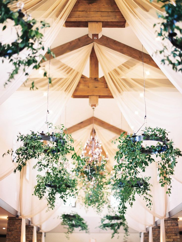 Natural romance, greenery-clad iron chandeliers, exposed beams, gauzy ivory curtains // Taylor Lord Photography