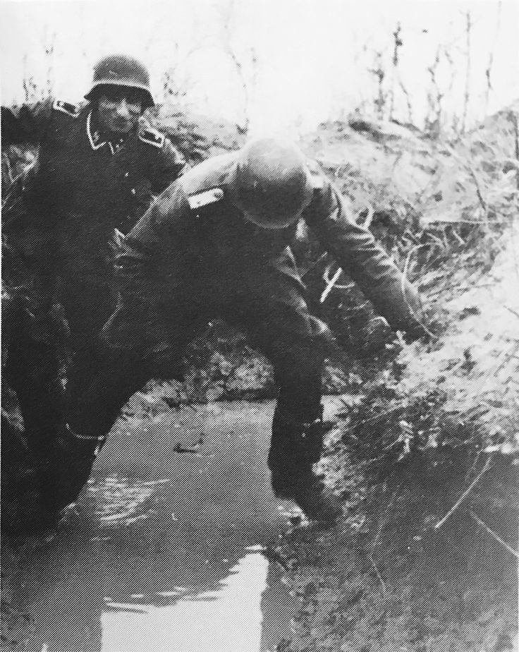 SS Volunteers from the Dutch Volunteer Legion getting trough fluded trenches.