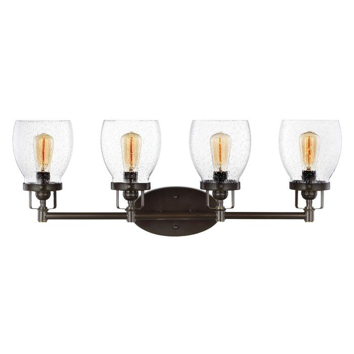 This 4 light vanity fixture in heirloom bronze offers shadow-free lighting in your powder room, spa, or master bath room. Influenced by the vintage industrial designs of early 20th Century America, the transitional lighting collection has seeded glass shades that highlight the classic Edison bulbs. The rich heirloom bronze finish adds another layer of retro design to the warm look. Incandescent medium-base lamping.