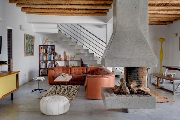 Converted factory home. Industrial, eclectic, modern, boho. Great contemporary fireplace and curved tan leather sofa. So much to love!