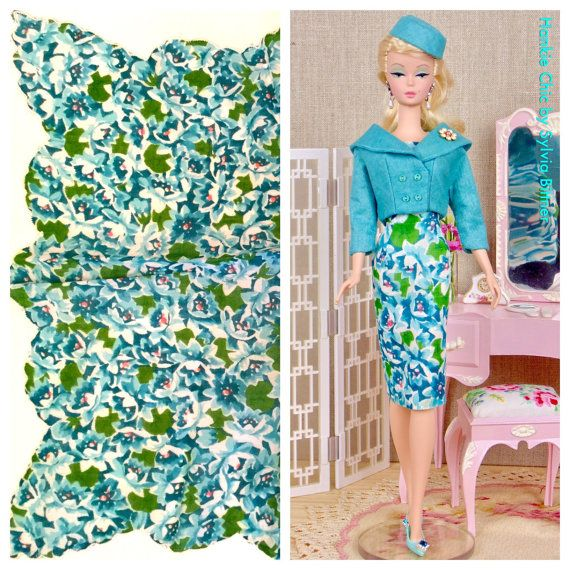 This lovely, fully lined suit features a cropped, double breasted jacket over a classic sheath dress with a coordinating pillbox hat.  The scoop neck dress is made from a vintage printed hankie with a floral print in shades of aqua blue with touches of pink. The jacket features a shawl collar, buttons over snap closure, and an attached brooch. A classic pillbox hat tops off the look.  This fashion was sewn entirely by hand from a vintage printed hankie, a coordinating aqua linen hankie and…
