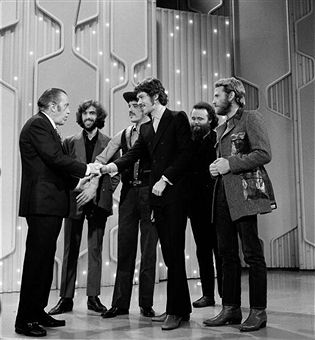The original members of Southern-style rock combo The Band, (from left) Canadians Richard Manuel, Rick Danko, Robbie Robertson, Garth Hudson and American Levon Helm, greet variety show host Ed Sullivan (1902 - 1974) (left), New York, November 2, 1969.