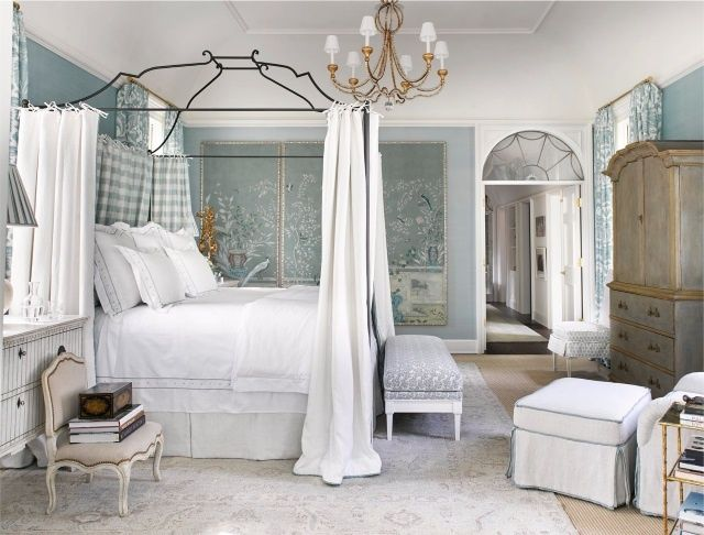 A gray Oushak rug brings out the beauty of the white canopy bed, grey and white bench and blue Chinoiserie wall covering