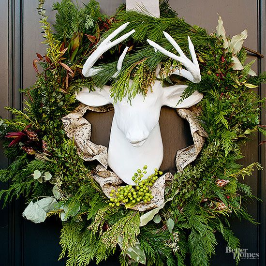 Our most festive front door starts with a faux white reindeer surrounded by green leaves and branches.  Anchor the wreath with a neutral ribbon and pops of bright green berries.