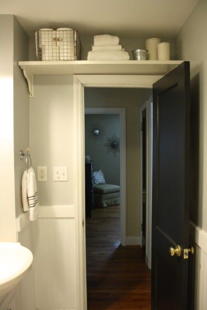 Over the door storage for a small Bath When you live in an old home with minimal storage you have to become creative with finding extra storage. Our bathroom for example has a teny tiny vanity with limited space and no linen closet. To maximize space in the bath we added a shelf over the door to store extras like toilet paper and extra towels. What a difference such a small change can make! WE ARE DOING THIS!!!! LW
