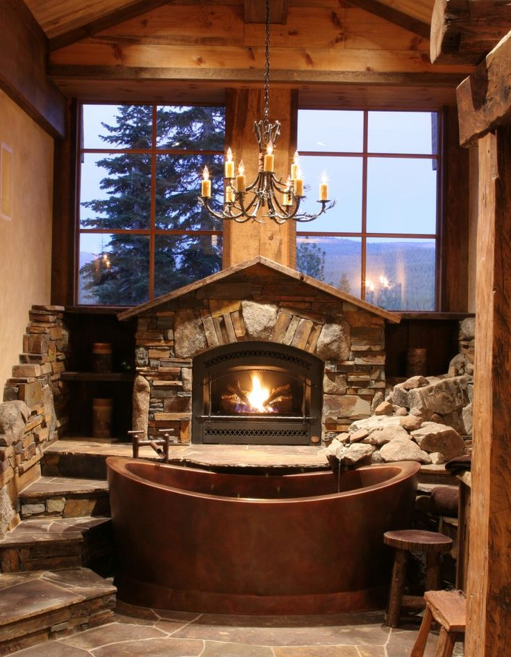 Copper bath tub with a fire place and hanging chandelier for Fireplaces bath