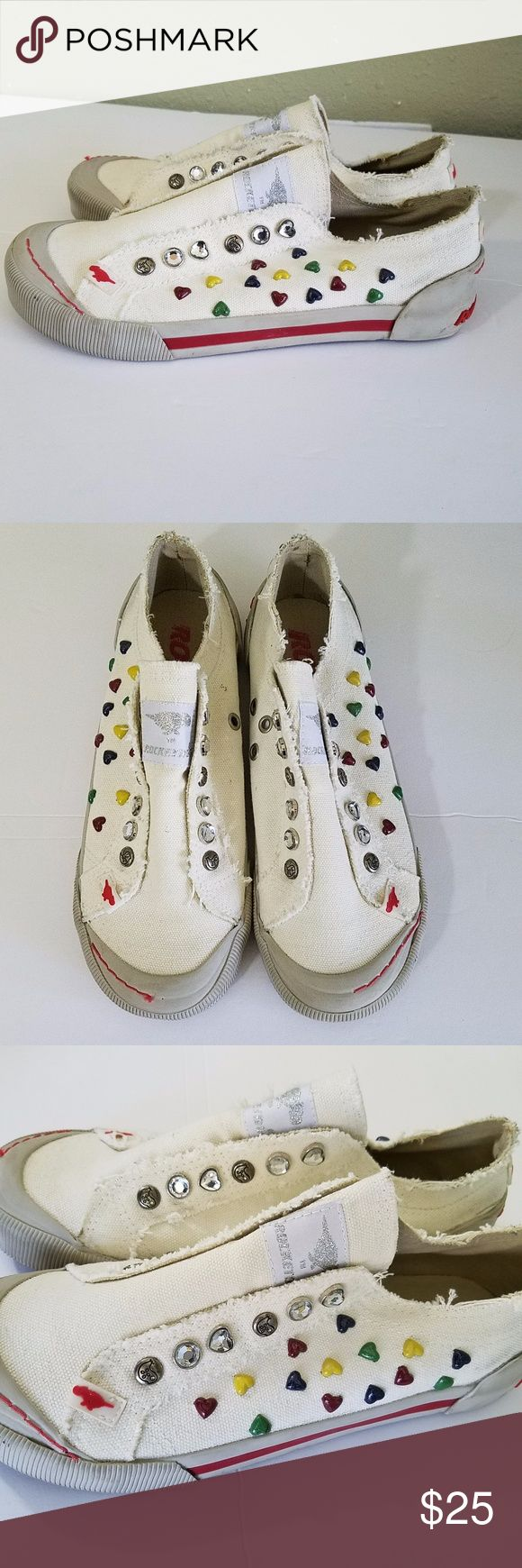"""Rocket Dog slip on tennis shoes 7 Hearts cream Rocket Dog slip on shoes.  No laces.  Frayed edges.  In good used condition.  A few minor marks.  In the eyelets it has bling buttons and the sides have heart embellishments. .  A size 7.   They measures 10"""" heel to toe on the outside bottom.  They are off white. Rocket Dog Shoes Athletic Shoes"""