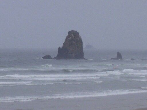 Needles at Cannon Beach, Oregon with Tillamook Rock Lighthouse in the distance.  A Travel Guide to Murder