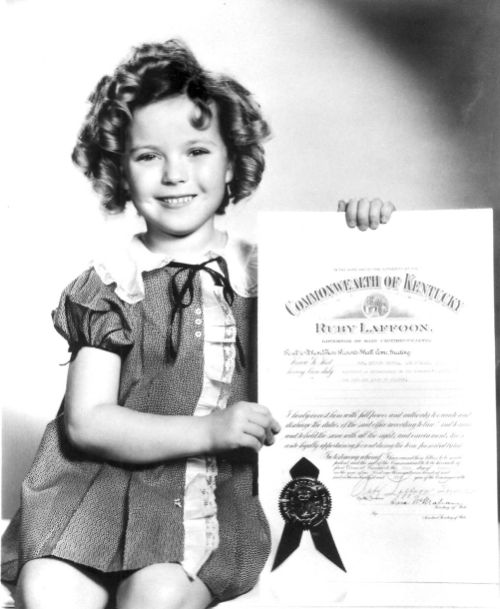 Shirley Temple, with papers declaring her an Honorary Kentucky Colonel, 1935.