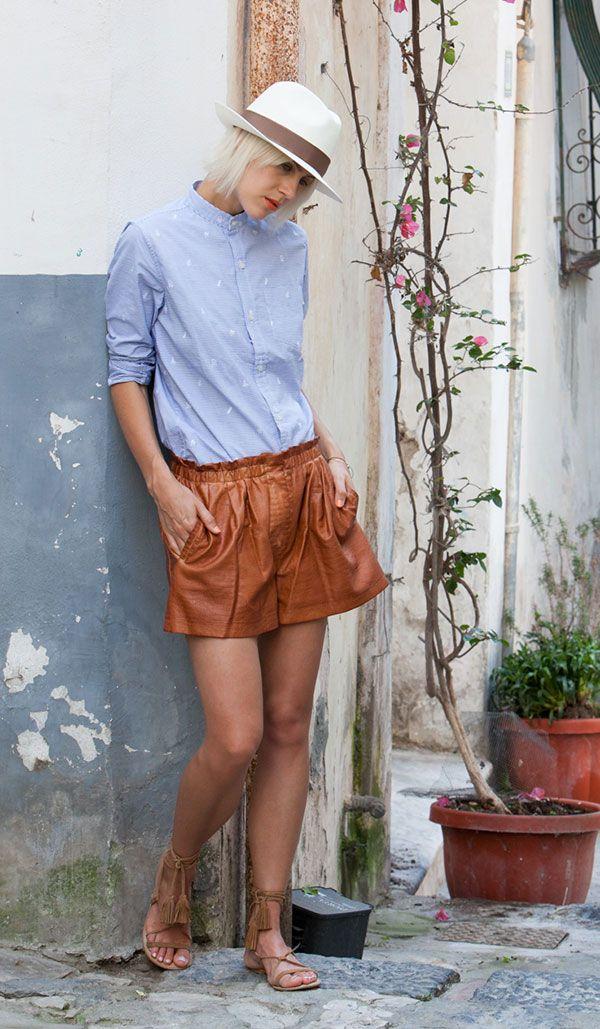 Linda Tol usa shorts couro marrom/caramelo com camisa azul em look street style look