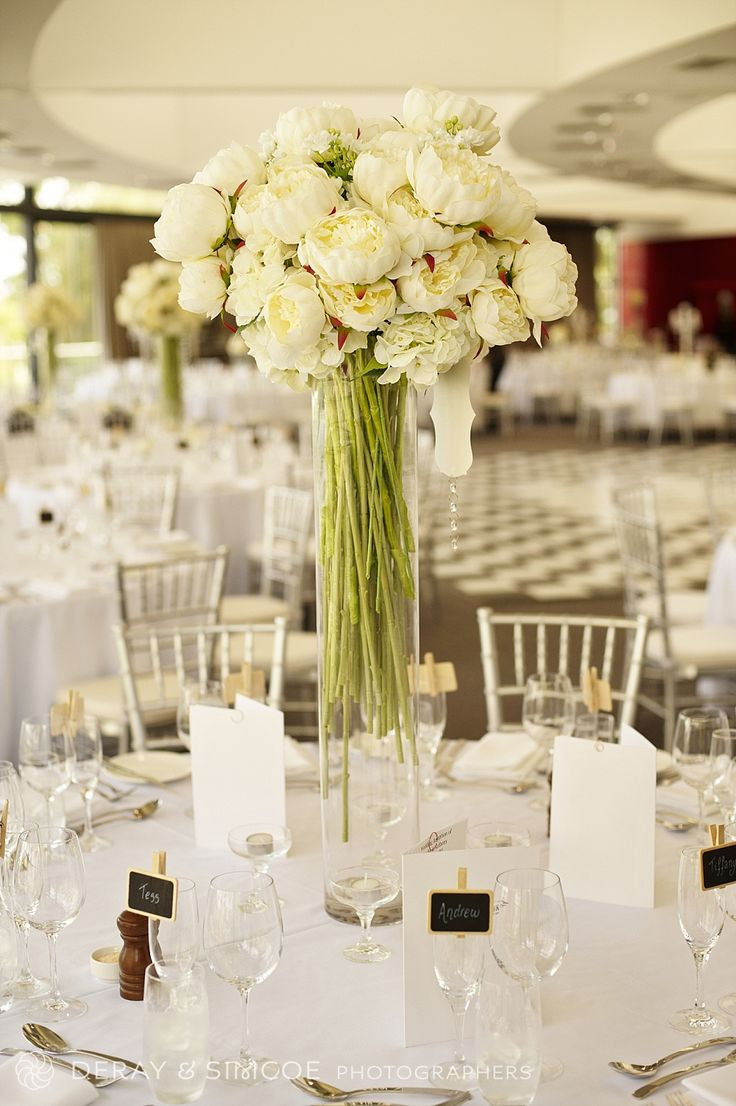 Long stemmed white peonies. Wedding reception table center piece