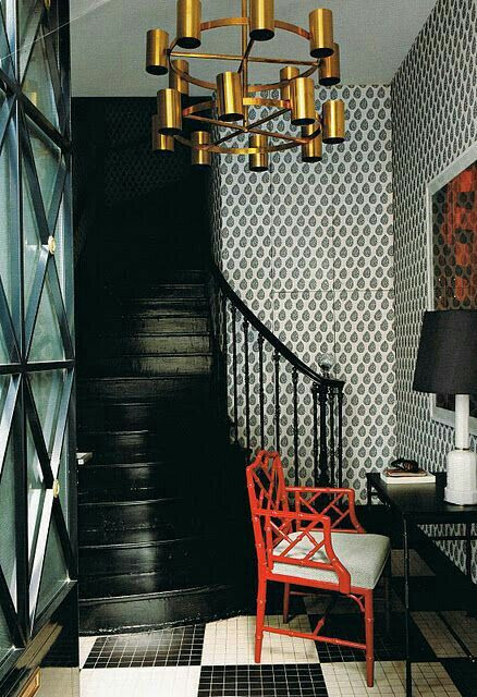 Black staircase with white n black wallpaper n red chair with golden headlamps on ceiling its adds n new n modern classical theme