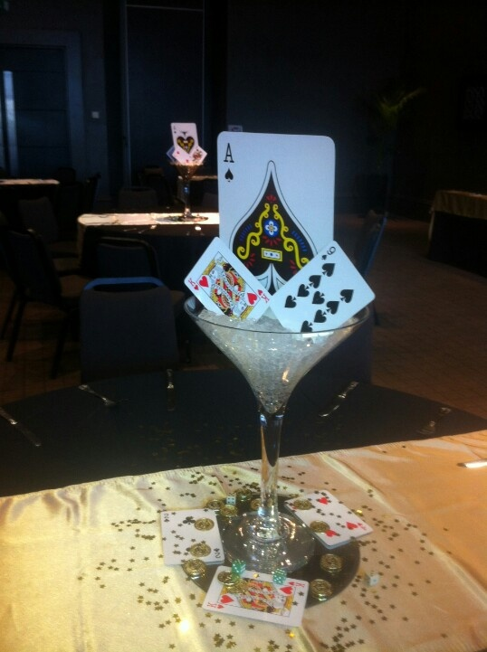 www.la-occasion.com - James Bond Themed Party  Martini Vase with clear gel inside and XXL playing cards and XL Playing Cards placed inside.  Placed on top of a round mirror with XL Playing Cards scattered around with dollar golden confetti. Placed on top of a Gold Satin table runner.