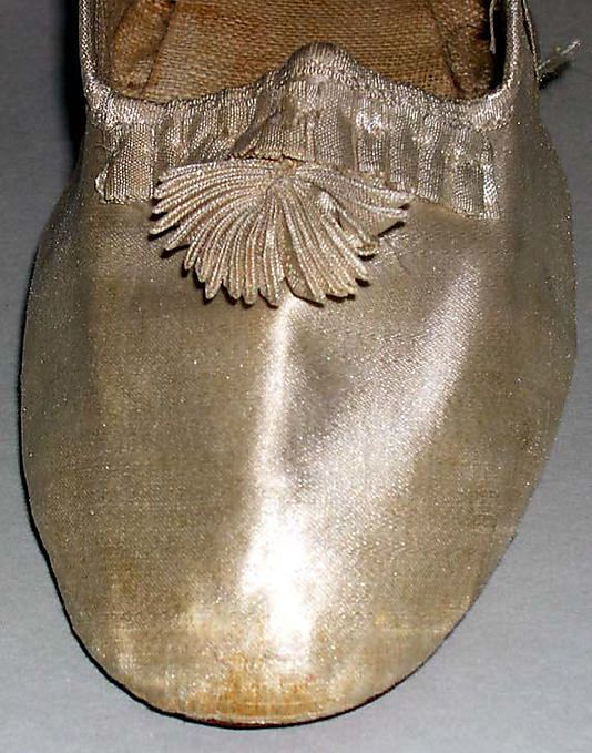 Slippers, 1810s, American, leather (and silk satin?) in The Metropolitan Museum of Art. Pictures of full shoes available, but I love this close-up of the self ribbon decoration!