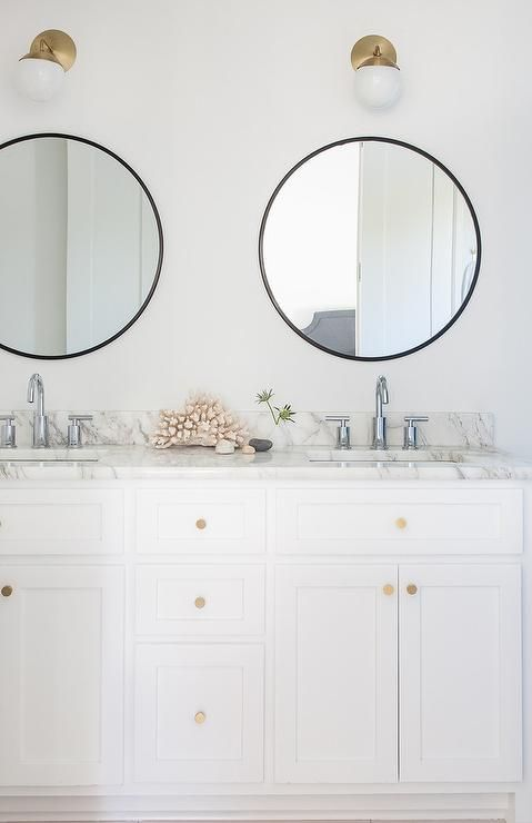 White and black bathroom features a white dual washstand adorned with brushed brass knobs topped with gray and white marble fitted with his and hers sinks and polished nickel faucets placed under round black mirrors and white glass and brass globe wall sconces, Cedar & Moss Alto Sconces.