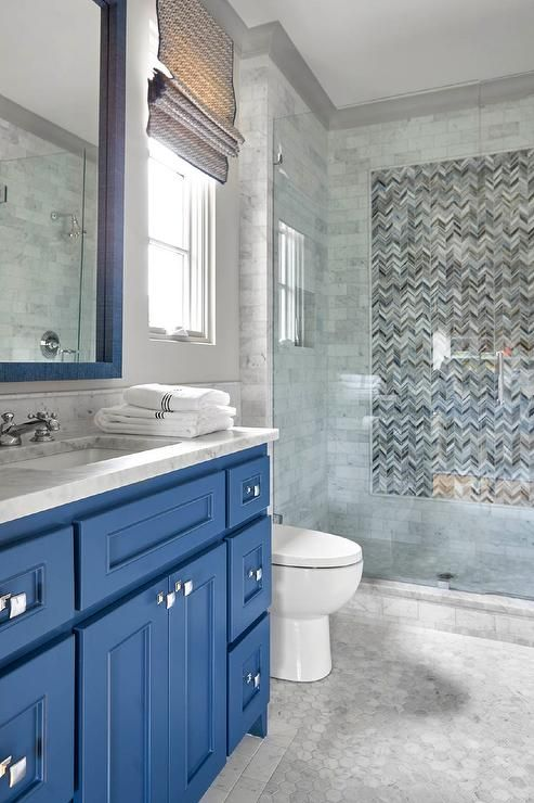 A blue washstand fitted with polished nickel square knobs and a gray marble countertop holding a sink with a polished nickel faucet beneath a blue framed vanity mirror.