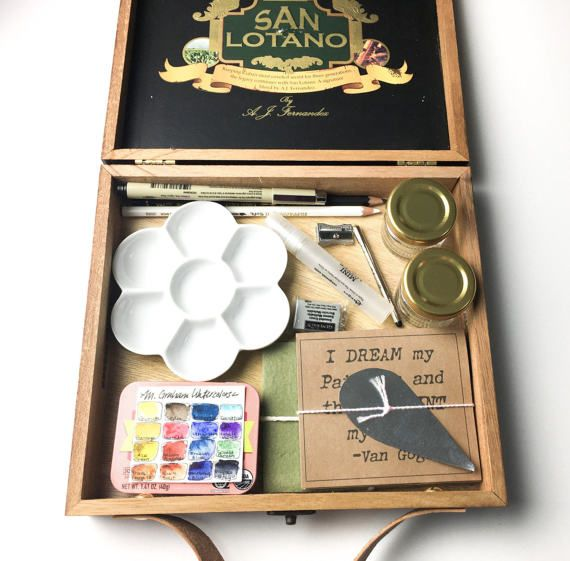 A collection of M Graham Watercolor necessities in a San Lotano cigar box. On the outside lid of the wooden box are yellow and green painted triangles. A Tan leather handle has been added for easy portability.  Included in this wooden cigar box you will find:  • 16 M Graham Watercolors in a hinged metal mint tin that measures 3.125 x 2.375 x .75 inches and each paint spot is .5 inches in diameter. (Included colors are: Bismuth Yellow, Gamboge, Azo Green, Transparent Orange Oxide, Sepia…