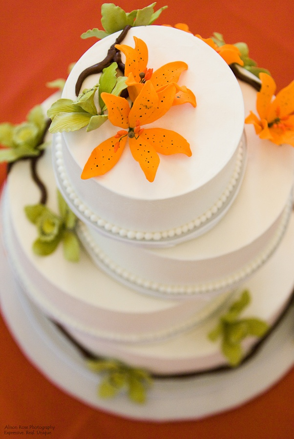 Fun wedding cake with orange and green flower accents
