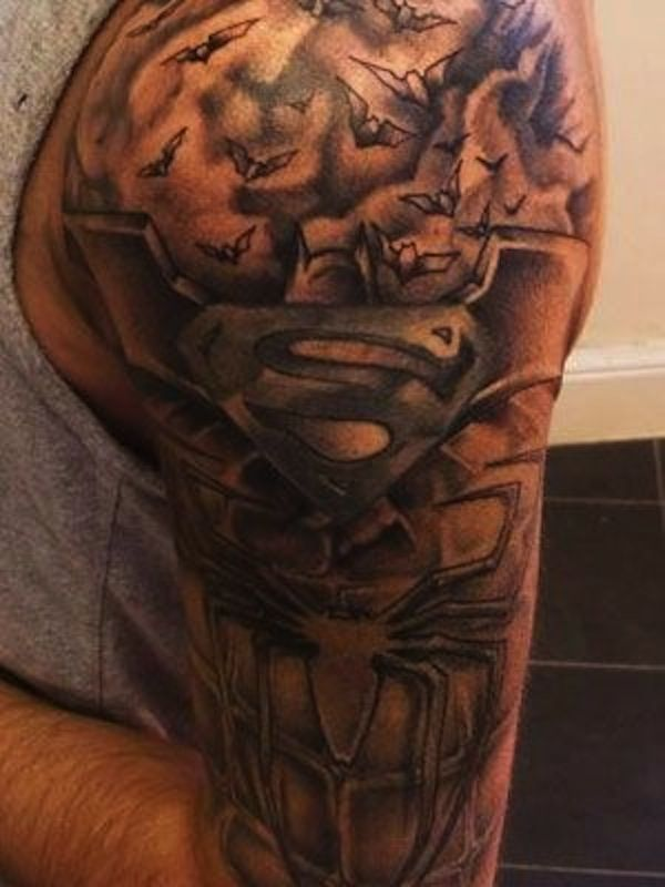 A charcoal inspired tattoo of Superman along with other heroes such as batman and Superman. The Collage of the superheroes' iconic signs looks amazing and truly eye catching.