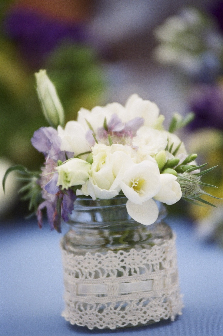 Beautiful wedding decorations - jars wrapped in lace and filled with a few pretty flowers