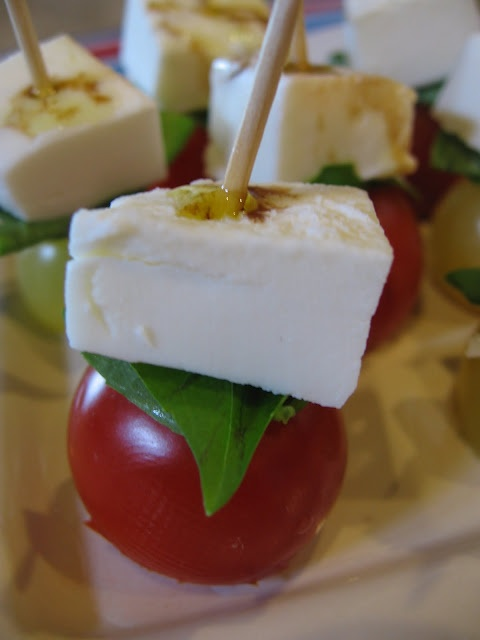 mozzarella, basil, and tomato on a toothpick drizzled with olive oil and balsamic