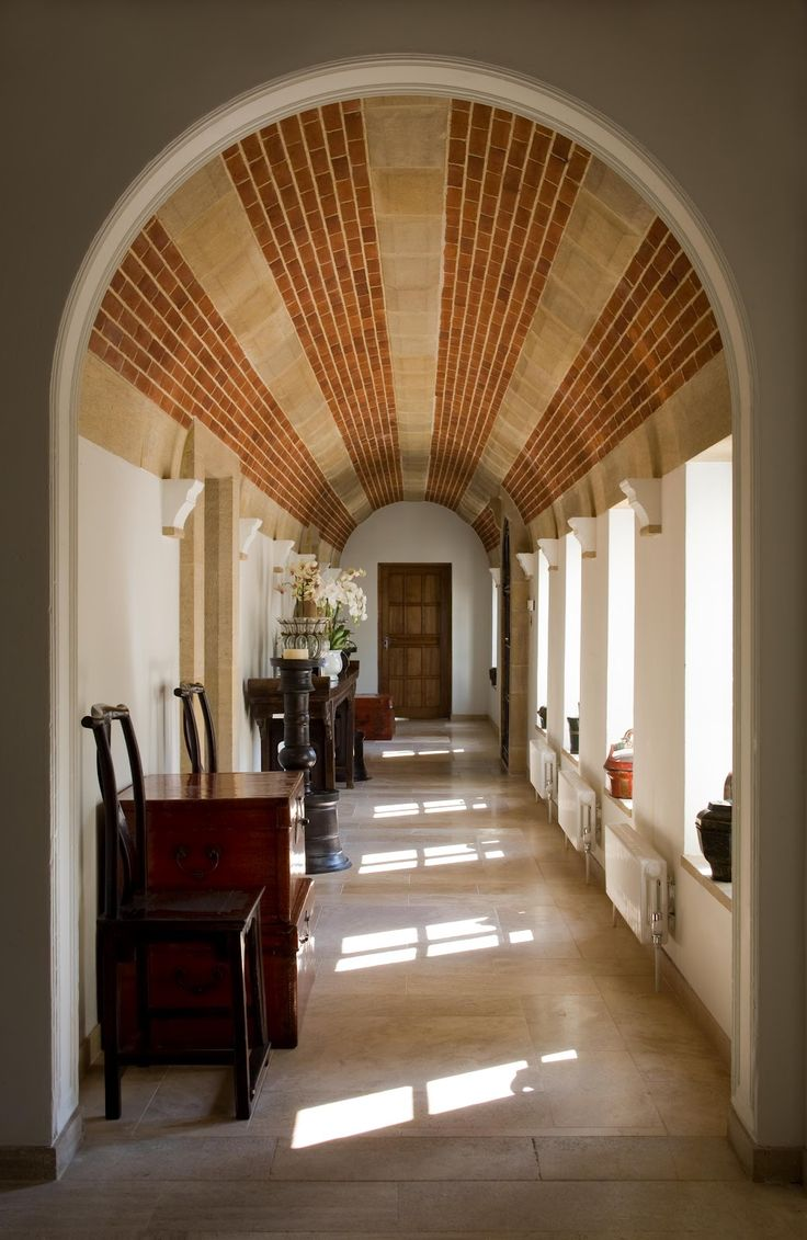 Barrel vault ceiling hallway - brick alternated with concrete to creates  stripes that carry your eye