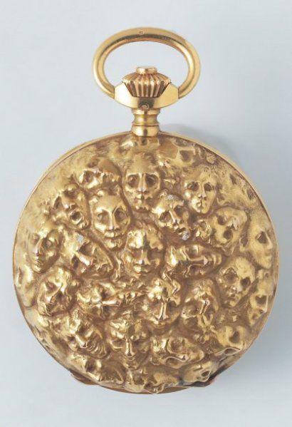 LALIQUE   MONTRE DE POCHE en or jaune. Le boîtier savonnette est orné de masques, d'après un dessin de Rodin. Mouvement classique, remontoir au pendant. Vers 1900. Diam. : 5 cm. Signée LALIQUE