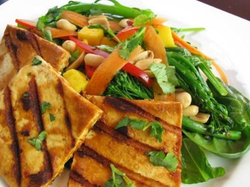 Grilled Spicy Peanut Tofu Steaks & Mango Spinach Broccolini Salad Recipe Salads, Main Dishes with firm tofu, natural peanut butter, hot water, tamari soy sauce, lime juice, chili sauce, broccolini, red pepper, shredded carrots, baby spinach, mango, salted roast peanuts, chopped cilantro, mango nectar, fresh lime juice, dijon mustard, olive oil, agave nectar, salt, pepper