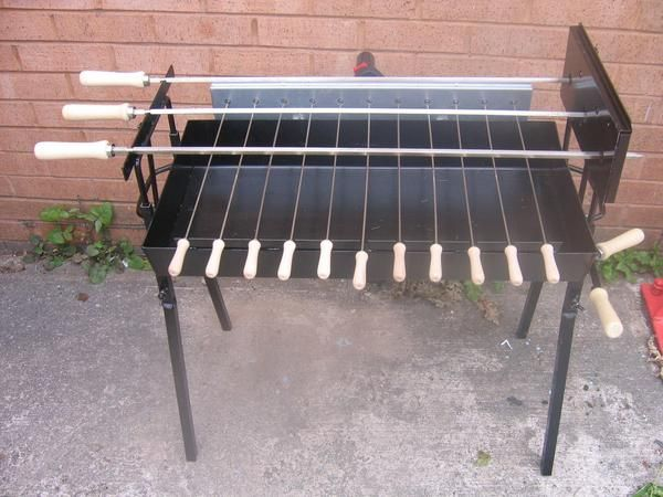 This modern version of the Cypriot BBQ Foukou is a slightly widerdesign than the standard traditional blue rotisserie barbecue. The main difference is the large skewers sit side by side on the same level as opposed to two skewers below and one on top. Extra Wide - Modern Cyprus Foukou Charcoal BBQ Set