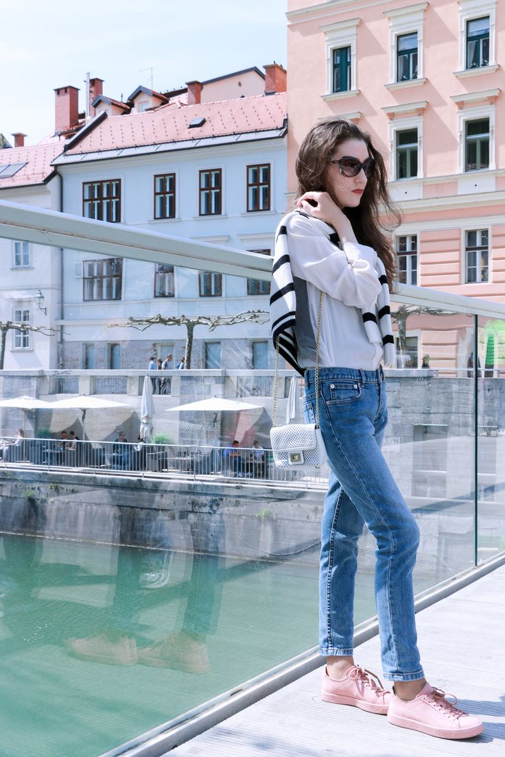 Fashion blogger Veronika Lipar of Brunette From Wall Street standing on the bridge wearing light blue jeans, pale pink sneakers, black and white striped top, and white mini bag
