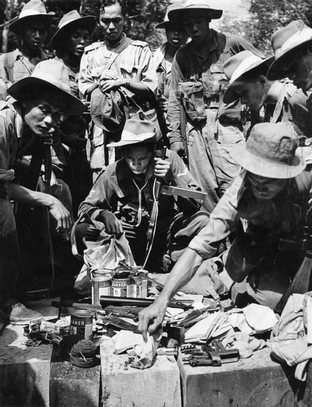 Troops of Malay Regiment inspecting captured communist equipment, Malaya, 1949