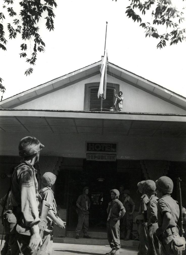 De roodwitte republikeinse vlag wordt door de Nederlandse militairen van de mariniersbrigade neergehaald van de gevel van hotel Republiek in Loemadjang tijdens het begin van de eerste politionele actie, Oost-Java Indonesië, 22 juli 1947.