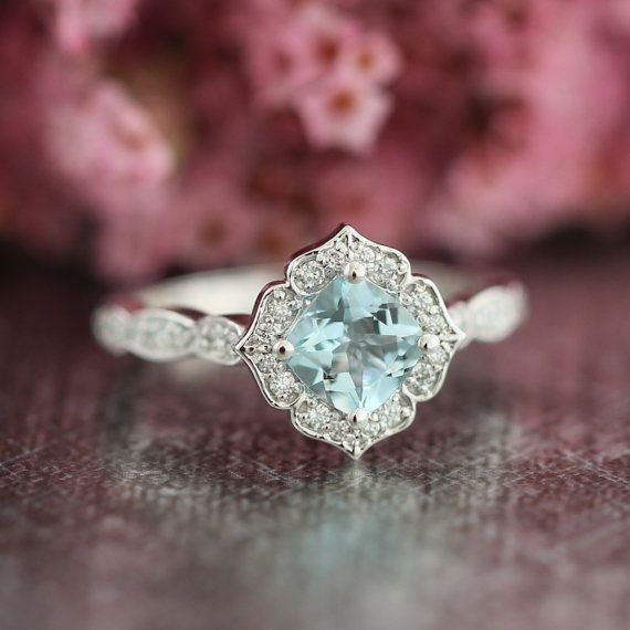 This mini vintage inspired aquamarine engagement ring features a 6x6mm cushion cut natural aquamarine set in a solid 14k white gold floral setting