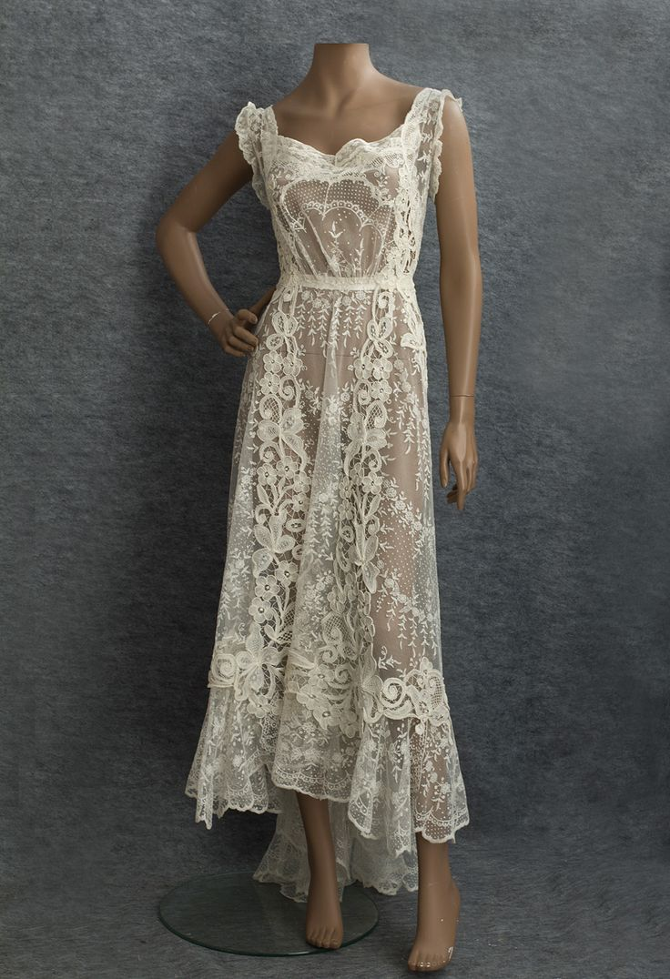 97 Circa 1910 Mixed Lace Wedding Dress made from delicate embroiderednet lace with bold accents of textured Quipure flowers. Click to seephoto details. Via Vintage Textiles. (Front)