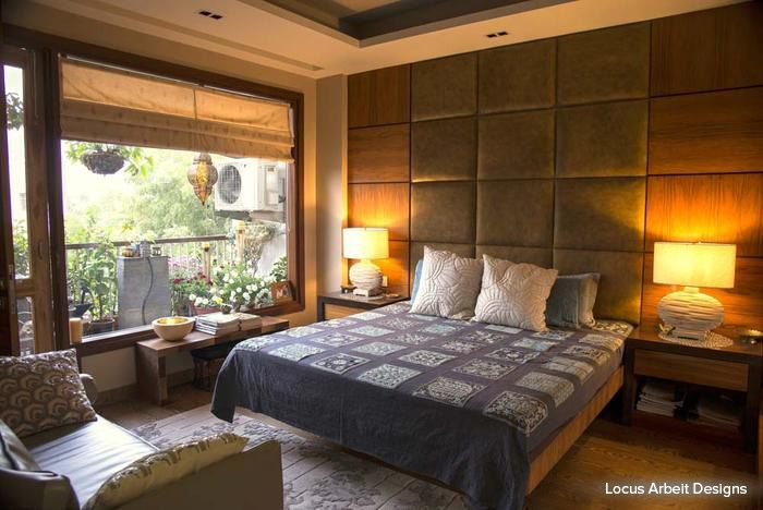 Wooden paneled walls, muted décor elements and striking table lamps, this bedroom is warm and inviting #bedroom #homedecor #contemporary  Design Courtesy - Locus Arbeit Designs, Delhi