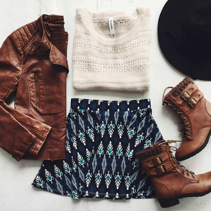 Brown Leather Look Jacket with Matching Brown Ankle Boots, a Knitted Sweater in White with a Cool Patterned Skirt on the Bottom, and a Jet Black Wide Brim Hat to Finish