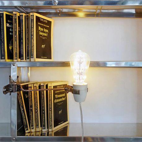 Lampe à pincer design @tsetseassocies - Une jolie douille en porcelaine blanche orientable fixée sur une pince d'acier, c'est en toute sobriété que la lampe Apollo vient illuminer votre intérieur. Astucieuse, la lampe Apollo est munie d'une pince en métal permettant de l'accrocher sur de multiples supports : rebords d'étagères, bibliothèques, tables ...