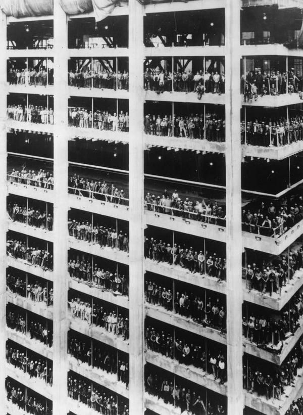 3,000 men who helped build the Chase Manhattan Bank stand in the window spaces of the building, 1964.