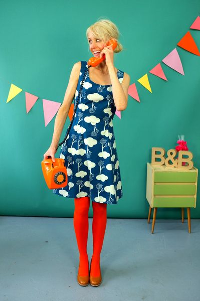 BAUMWOLLKLEID.  The bright orange tights give an edge to what could otherwise be an overly sweet dress.