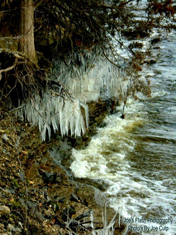 Waves hitting up against these Icicles on the shores of the Mighty Moira river Belleville Ontario as Floodwaters ravage the River in the torrant
