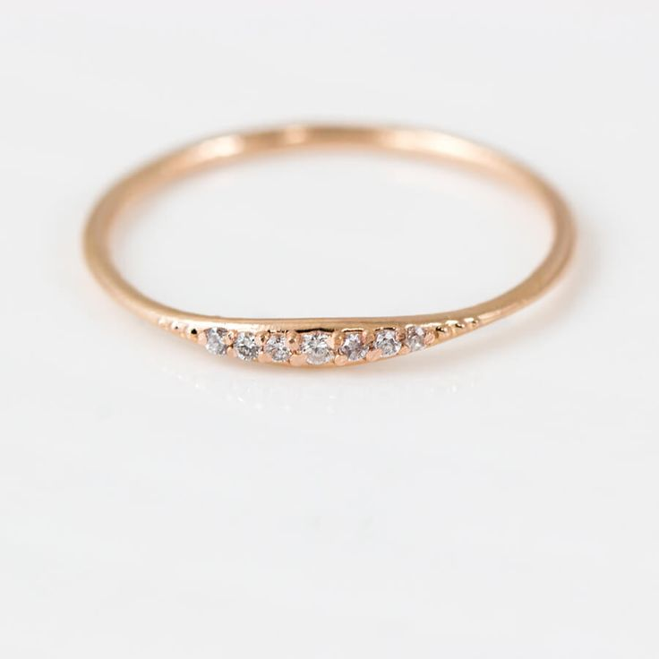 Thin line stacking ring with seven tiny white diamond in solid 14k rose gold. Handmade stacking ring by Melanie Casey.