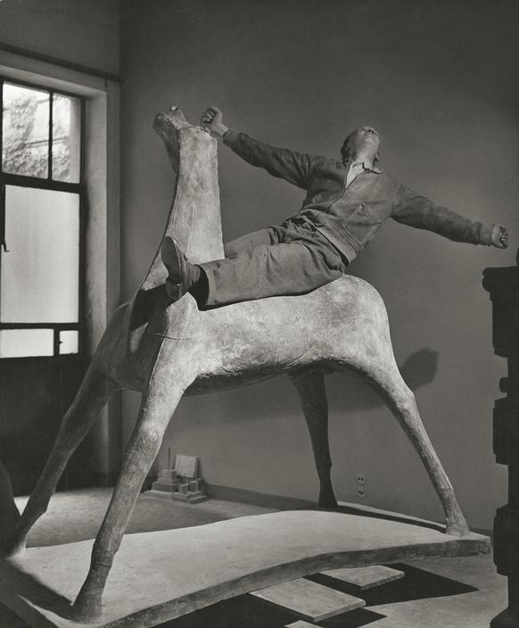 Marino MARINI, in his studio on one of his horses. Milan Italy 1952.  Herbert List