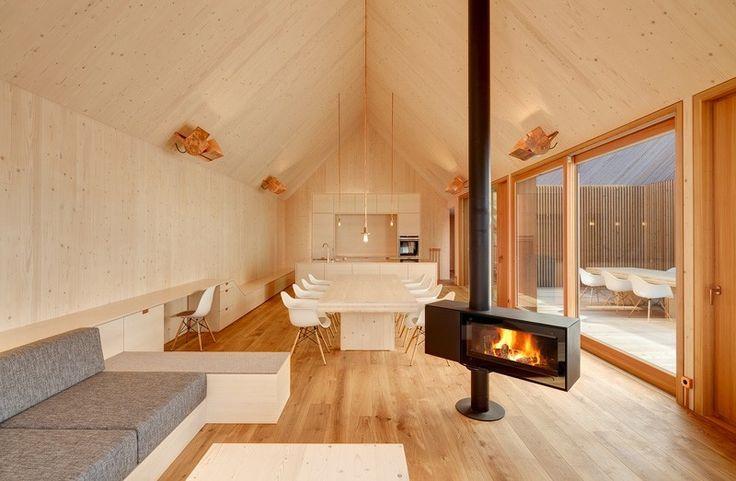 cheminée centrale en métal gris foncé, meubles blancs et canapé en tissu gris signée Kuehlein Architektur