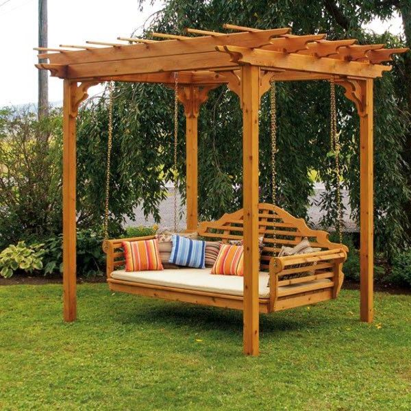 Garden swing under a small wooden pergola near trees