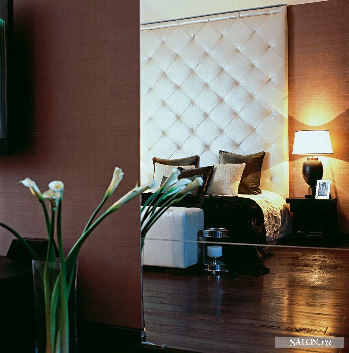 Кровать сделана по специальному заказу: у неё высокое изголовье, а также прикроватный пуф в изножье. Стены спальни отделаны шёлковыми обоями Vescom.   Настольная лампа, Sigma L2