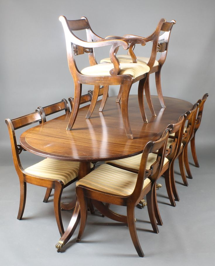 """Lot 899, A Georgian style mahogany dining suite comprising triple pillar D end extending dining table with 2 extra leaves inlaid with brass crossbanding 29""""h x 38 1/2""""w x 90 1/2""""l  x 133 1/2""""l with leaves  together with 10 bar back dining chairs - 8 standard, 2 carvers est £100-150"""