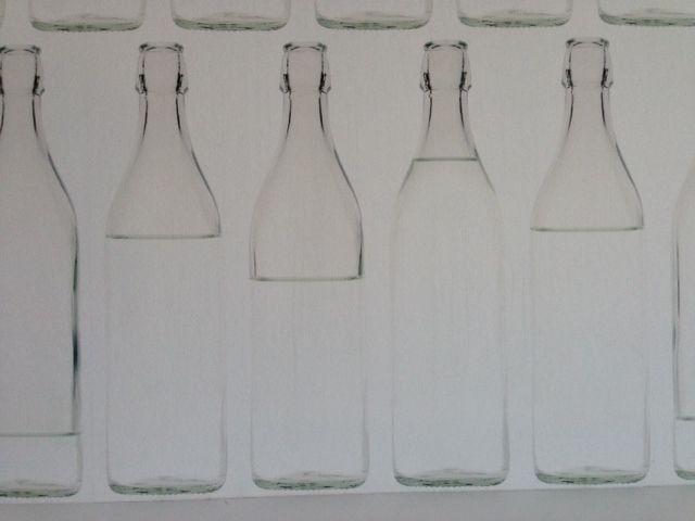 Detalle papel en pared . Botellas de leche...