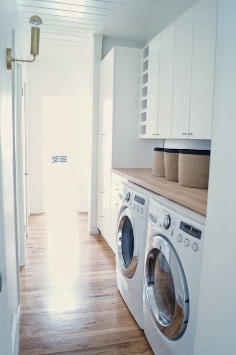 Amazing hall laundry room features white beadboard ceiling over white lacquered cabinets situated above white front-load washer and dryer topped with butcher block beside tall white lacquered cabinets used to store laundry products.